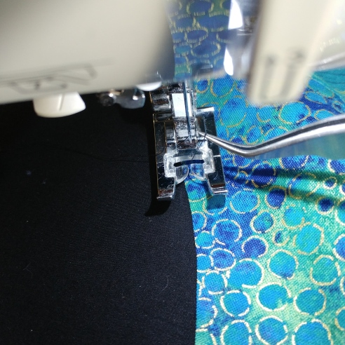 Tweezers to pull up bobbin thread to bury on machine applique
